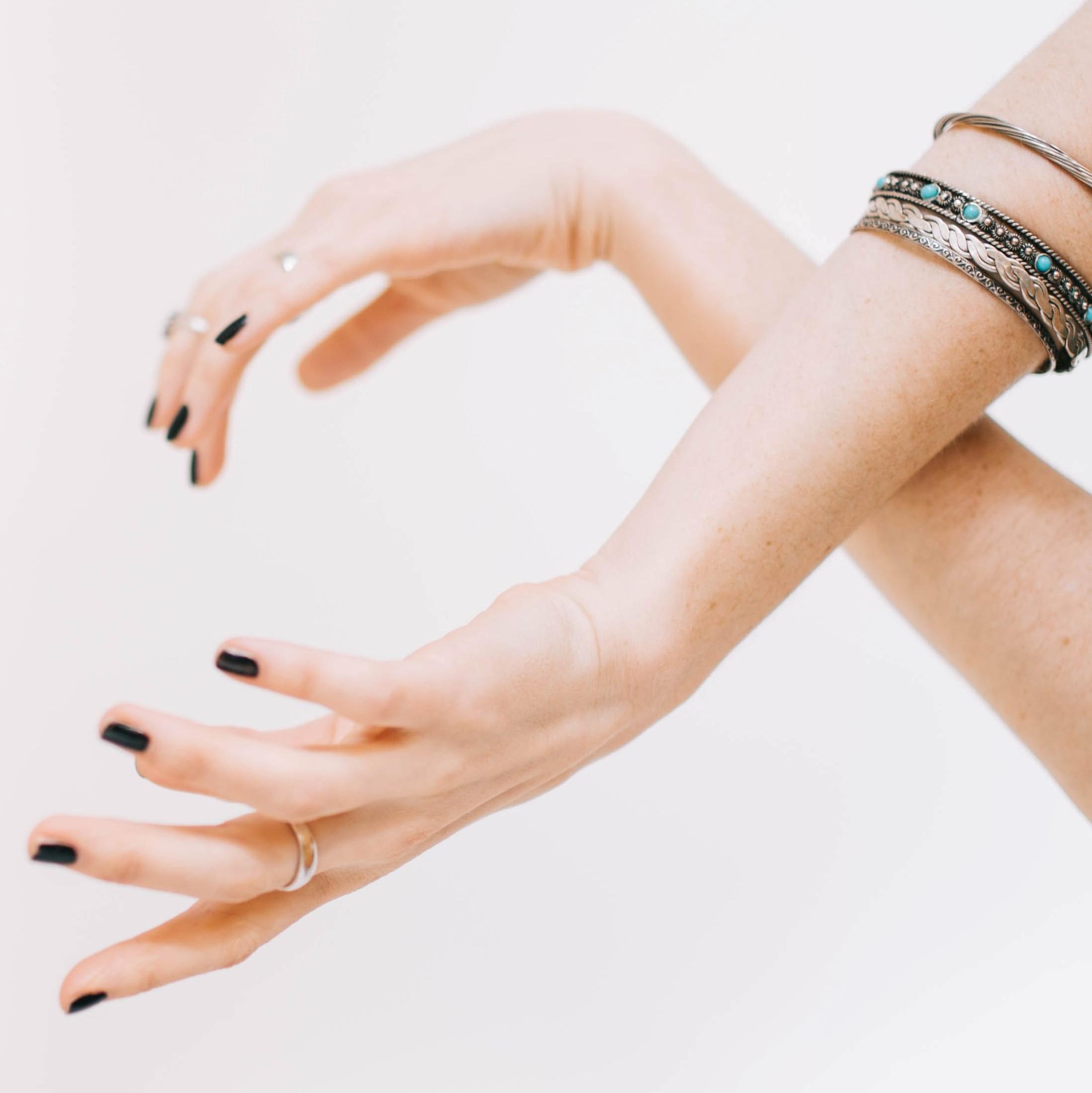 mains croisées vernis noir et bracelets